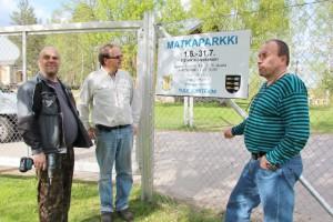 Mika Ikonen, Ilmo Utriainen ja Pekka Suhonen kiinnittivät opastekyltin koulun aitaan.