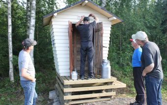 Tiehoitokunnan puheenjohtaja Raimo Putkonen naulaa kyltin paikoilleen .